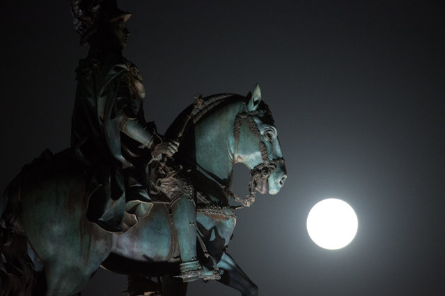 """A  so-called """"supermoon"""" full  moon rises behind the statue of Portuguese king Jose I in Lisbon's Comercio square Saturday, August 29 2015. (Photo by Armando Franca/AP Photo)"""