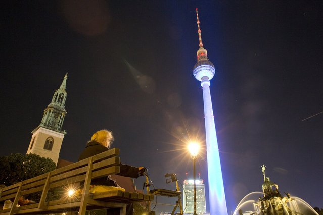 "An elderly woman sits in front of the illuminated TV Tower in Berlin, October 2, 2015. During the festival ""Berlin leuchtet"" (Berlin lights) a privately financed society iluminates several buildings in Berlin. (Photo by Axel Schmidt/Reuters)"