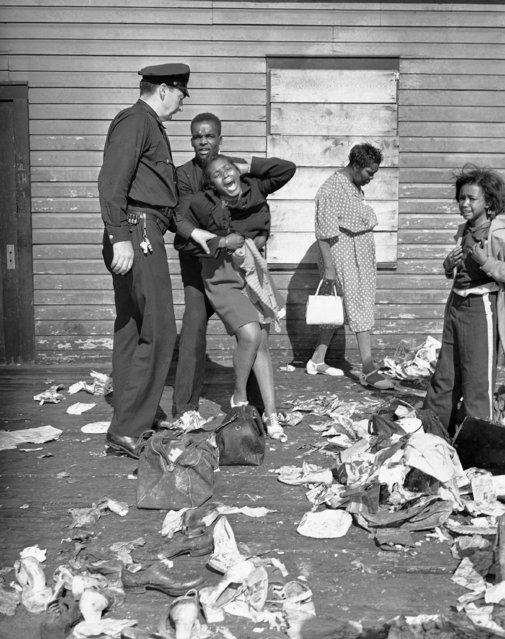 A hysterical woman is aided after she viewed the body of a relative who was trampled to death in a stampede at the 132nd Street pier of the Hudson River, August 17, 1941. The incident occurred when an estimated 10,000 Harlem residents showed up to board a boat for an excursion to Bear Mountain when there were only accommodations for 3,100. (Photo by Murray Becker/AP Photo)