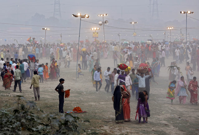 A vendor selling garlands waits for customers as Hindu devotees gather to worship the Sun god Surya on the banks of the river Yamuna during the Hindu religious festival of Chatt Puja in New Delhi October 29, 2014. (Photo by Ahmad Masood/Reuters)