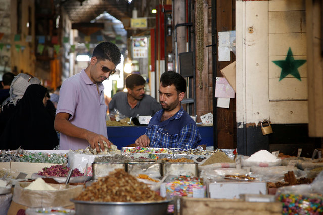 Men inspect sweets ahead of eid celebrations in al-Bazourieh Souq in Damascus, Syria September 10, 2016. (Photo by Omar Sanadiki/Reuters)