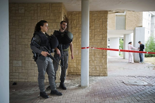Israeli border police officers guard next to a cordon near the scene of a stabbing attack in the southern town of Kiryat Gat, Israel October 7, 2015. (Photo by Amir Cohen/Reuters)