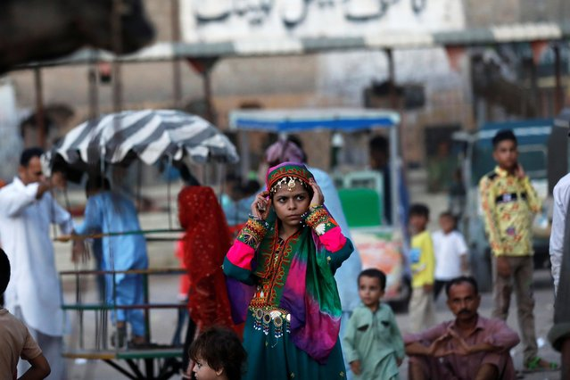 A girl in traditional attire adjusts her scarf at a playground in a slum during Eid al-Adha celebration, in Karachi, Pakistan on August 2, 2020. (Photo by Akhtar Soomro/Reuters)