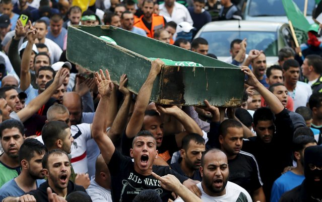 Mourners carry the body of 22-year-old Palestinian Ahmad Qali, who was shot by Israeli troops during clashes on Friday, during his funeral in the Palestinian refugee camp of Shuafat near Jerusalem October 10, 2015. (Photo by Ammar Awad/Reuters)