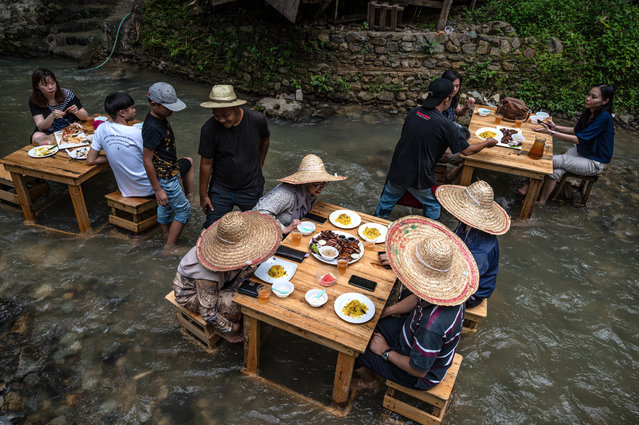 Customers eat lunch at a restaurant with tables in a stream of a river in Kampung Kemensah on the outskirts of Kuala Lumpur on July 14, 2020. (Photo by Mohd Rasfan/AFP Photo)