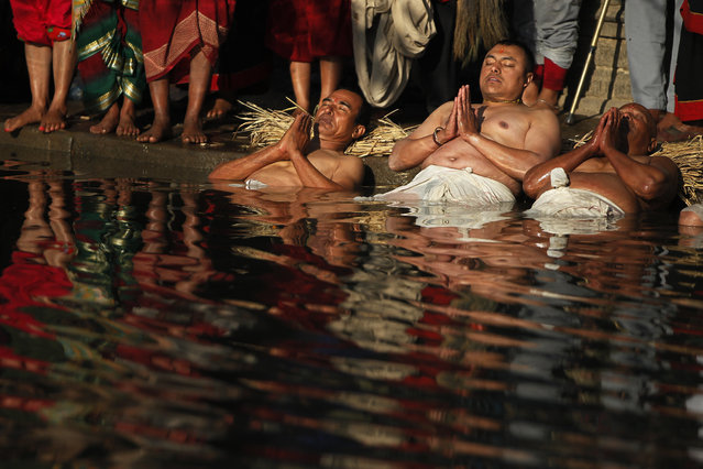 Nepalese Hindu devotees offer prayers while dipping half of their bodies into the Hanumante river during Madhav Narayan Festival in Bhaktapur, Nepal, Tuesday, January 2, 2018. During the festival devotees recite holy scriptures dedicated to the Hindu goddess Swasthani and Lord Shiva. Unmarried women pray to find a good husband while those married pray for the longevity of their husbands by observing a month-long fast. (Photo by Niranjan Shrestha/AP Photo)