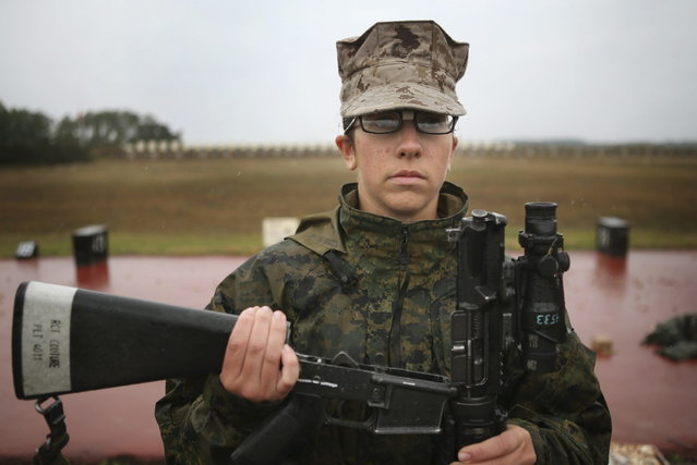 Marine recruit Melony Couture waits for her rifle to be inspected before firing on the rifle range during boot camp February 25, 2013 at MCRD Parris Island, South Carolina. Female enlisted Marines have gone through recruit training at the base since 1949. About 11 percent of female recruits who arrive at the boot camp fail to complete the training, which can be physically and mentally demanding. Females in the Marines and other branches of the armed forces have been forbidden from being assigned to ground combat units since 1994. On January 24, 2013 Secretary of Defense Leon Panetta rescinded that order. (Photo by Scott Olson/AFP Photo)