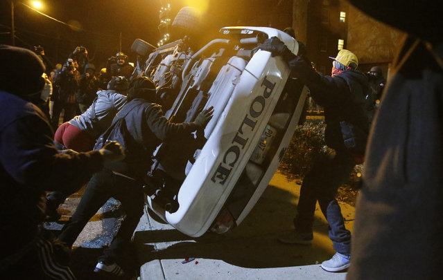 Protesters flip over a Ferguson police car in Ferguson, November 25, 2014. (Photo by Jim Young/Reuters)