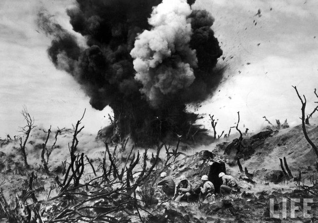 In a picture that captures the violence and sheer destruction inherent in war perhaps more graphically than any other ever published in LIFE, Marines take cover on an Iwo Jima hillside amid the burned-out remains of banyan jungle, as a Japanese bunker is obliterated in March 1945. (Photo by W. Eugene Smith/Time & Life Pictures)