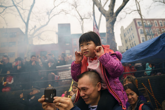 A young girl plugs her ears as the firecracker ceremony begins at a cultural festival to mark the first day of the Lunar New Year in Chinatown neighborhood in Manhattan, February 16, 2018 in New York City. The 2018 Chinese New Year, which is the year of the dog, begins on Friday and celebrations will last for over two weeks. (Photo by Drew Angerer/Getty Images)