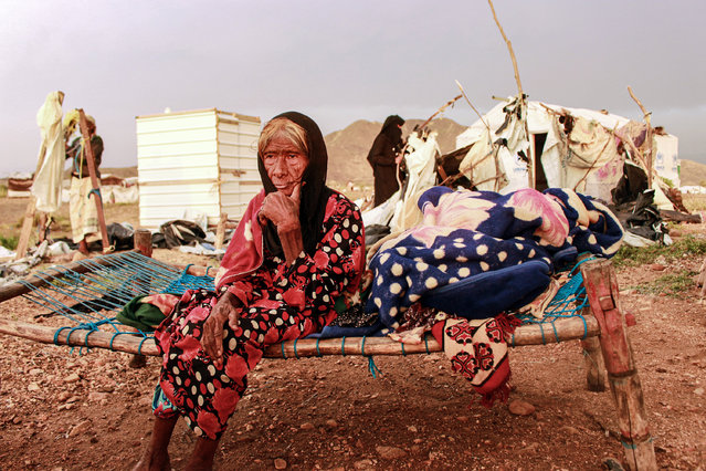 An elderly woman looks on while sitting on a make-shift bed as people try to salvage tents damaged by torrential rain, at a camp for Yemenis displaced by conflict in the northern Hajjah province on September 30, 2020. (Photo by Essa Ahmed/AFP Photo)