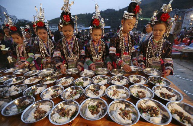 Ethnic minority Dong girls in traditional costumes have breakfast before attending a Kam Grand Choir competition in Congjiang county, Guizhou province November 28, 2014. (Photo by Sheng Li/Reuters)