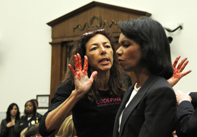 Secretary of State Condoleezza Rice, right, is confronted by Code Pink member Desiree Sairooz, her hands painted red, as she arrived to testify on Capitol Hill in Washington, on October 24, 2007, before the House Foreign Relations Committee hearing regarding US policy in the Middle East, where she spoke about Iraq, Iran, and the Israel Palestinian conflict. (Photo by Charles Dharapak/AP Photo/The Atlantic)