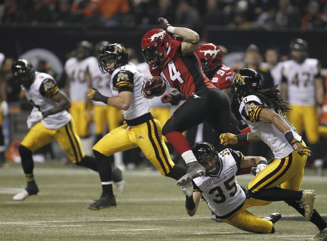 Calgary Stampeders' Matt Walter (C) jumps over Hamilton Tiger Cats' Mike Daly (35) during the first half of the CFL's 102nd Grey Cup football championship in Vancouver, British Columbia, November 30, 2014. (Photo by Andy Clark/Reuters)