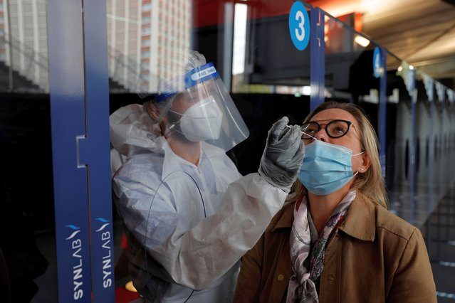 A health worker, wearing a protective suit and a face mask, administers a nasal swab to a patient in a temporary testing site for the coronavirus disease (COVID-19) at the Zenith Arena in Lille, France, October 15, 2020. (Photo by Pascal Rossignol/Reuters)
