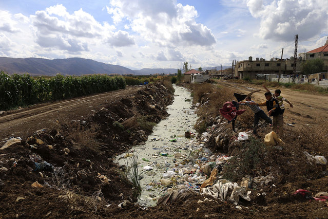 Syrian refugee boys throw trash into sewage water at a Syrian refugee camp in the town of Hosh Hareem, in the Bekaa valley, east Lebanon, Wednesday, October 28, 2015. The United Nations said Tuesday the worsening conflict in Syria has left 13.5 million people in need of aid and some form of protection, including more than six million children. (Photo by Hassan Ammar/AP Photo)