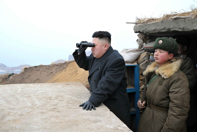 Kim Jong Un uses a pair of binoculars to look towards the South during his visit to the Jangjae Islet Defence Detachment and Mu Islet Hero Defence Detachment, southwest of Pyongyang, on March 7, 2013. (Photo by Reuters/KCNA)