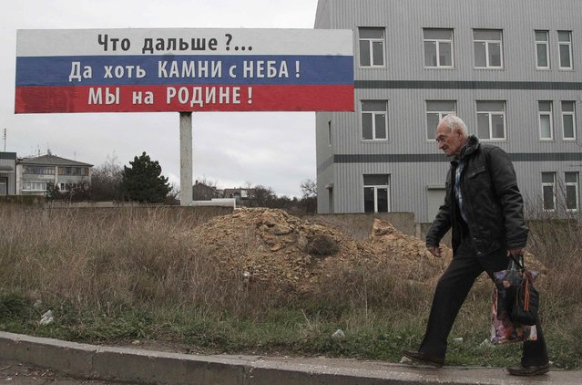 """A man carries a bag attached with an orange and black ribbon of St. George as he walks past a billboard in the Crimean port of Sevastopol, November 29, 2014. The billboard reads: """"What's next? At least the stones are from the sky! We are at home!"""" (Photo by Pavel Rebrov/Reuters)"""