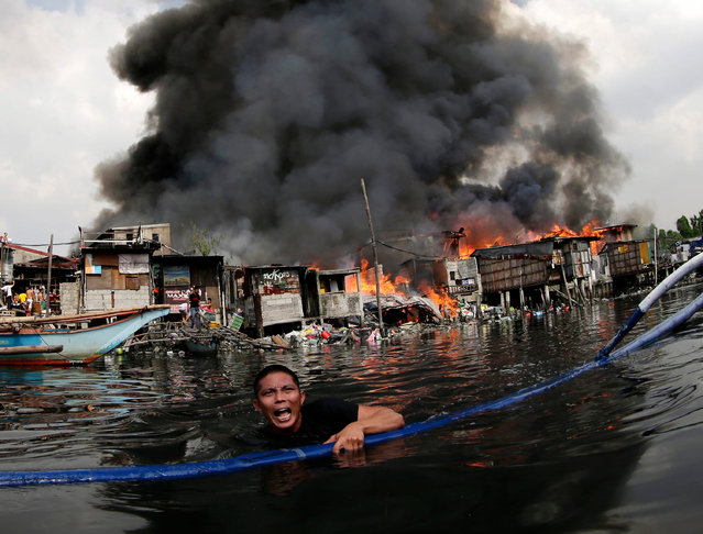Filipinos escape from a fire in Paranaque city, south of Manila, Philippines, 29 October 2015.. (Photo by Francis R. Malasig/EPA)