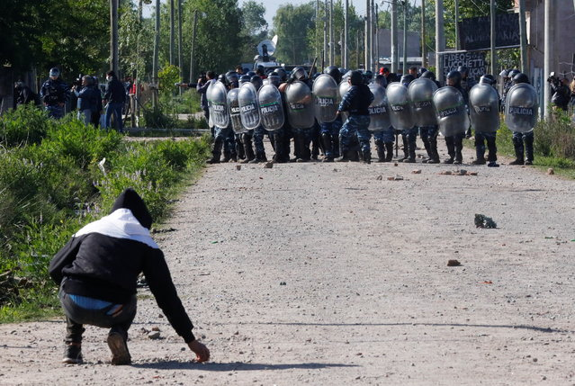 A man grabs stones from the ground as he confronts police officers carrying out an eviction at a squatters camp in Guernica, on the outskirts of Buenos Aires, Argentina on October 29, 2020. (Photo by Agustin Marcarian/Reuters)