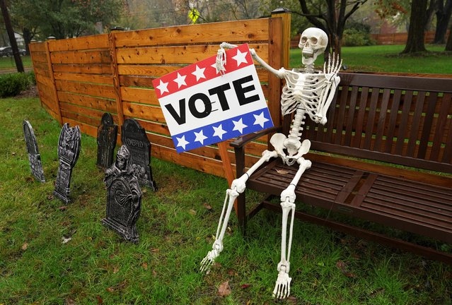 With less than a week before Election Day, a Halloween skeleton holds a vote sign outside a home in Falls Church, Virginia, October 29, 2020. (Photo by Kevin Lamarque/Reuters)