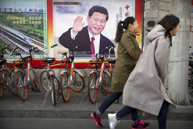 In this Friday, March 2, 2018, photo residents walk past a poster showing Chinese President Xi Jinping in Beijing. (Photo by Mark Schiefelbein/AP Photo)