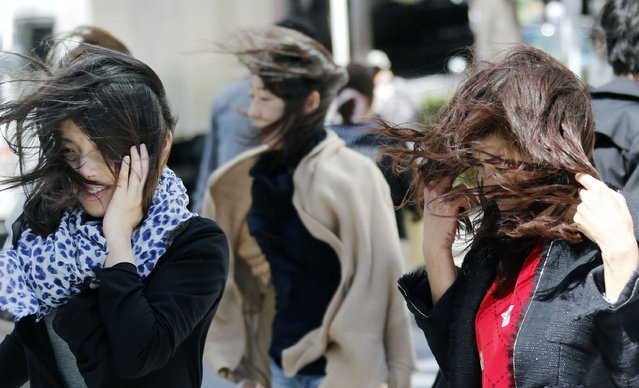Women try to keep their hair in order in Tokyo, Japan as strong winds buffeted the city on Sunday, April 7, 2013. (Photo by Koji Sasahara/AP Photo)