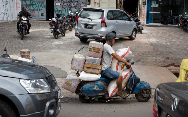 A man carries fuel and rice on his motorbike as he drives through central Jakarta, Indonesia, Thursday, December 11, 2014. There are an estimated 70 million motorbikes or nearly 80 percent of all registered vehicles on the roads of Indonesia, with that number growing by approximately ten percent annually. (Photo by Mark Baker/AP Photo)