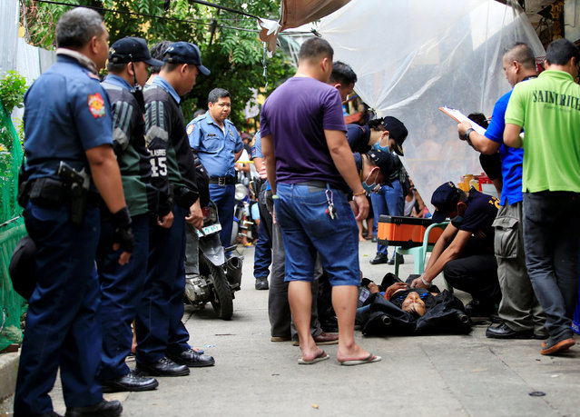 Members of the Philippine National Police (PNP) investigation team inspect the body of a suspected drug pusher who was killed in a police operation in metro Manila, Philippines October 8, 2016. (Photo by Romeo Ranoco/Reuters)