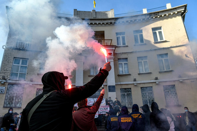 """Workers of """"Tavria Research Farm"""" SE and representatives of the National Corps hold hand flares during the protest action to demand closure of the case on bankruptcy of the agricultural enterprise outside the Commercial Court building, Zporizhzhia, southeastern Ukraine on October 9, 2020. (Photo by Ukrinform/Rex Features/Shutterstock)"""