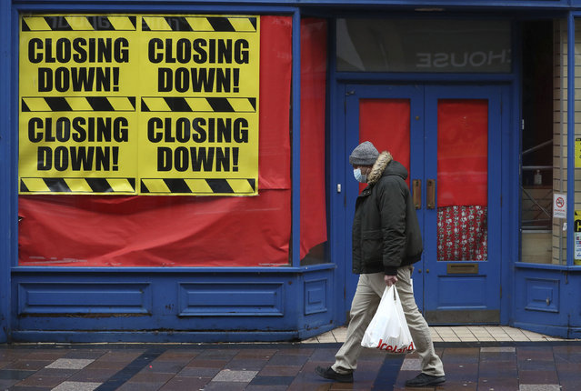 A man wearing a face mask to protect against coronavirus, walks past a closed shop in Stirling, Scotland, Sunday, November 15, 2020. Scotland are currently using a tier system to try and drive down coronavirus cases. (Photo by Andrew Milligan/PA Wire via AP Photo)