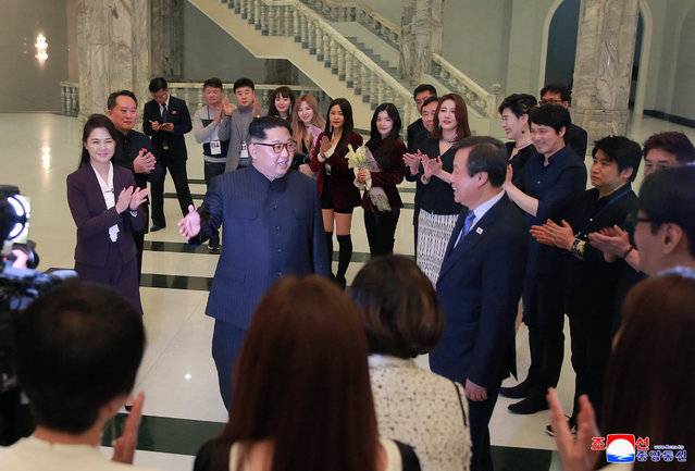 """In this photo provided by the North Korean government, North Korean leader Kim Jong Un, center left, talks with South Korean Culture, Sports and Tourism Minister Do Jong-whan, center right, as his wife Ri Sol Ju, left, claps during a visit to members of a South Korean artistic group after their performance in Pyongyang, North Korea, Sunday, April 1, 2018. Kim clapped his hands as he, along with his wife and hundreds of other citizens, watched the rare performance Sunday by South Korean pop stars visiting Pyongyang, highlighting the thawing ties between the rivals after years of heightened tensions over the North's nuclear program. Independent journalists were not given access to cover the event depicted in this image distributed by the North Korean government. The content of this image is as provided and cannot be independently verified. Korean language watermark on image as provided by source reads: """"KCNA"""" which is the abbreviation for Korean Central News Agency. (Photo by Korean Central News Agency/Korea News Service via AP Photo)"""