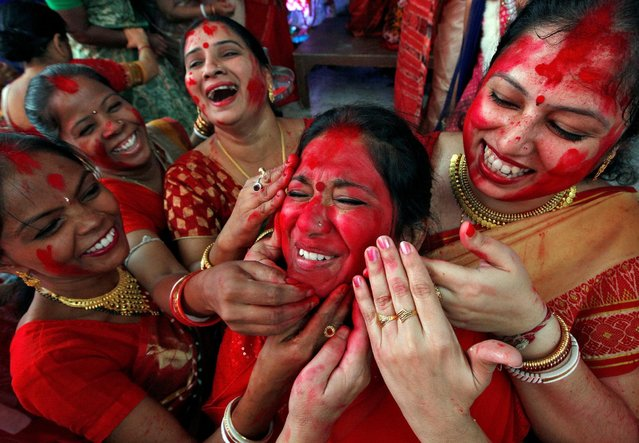 "Hindu women apply ""sindhur"", or vermillion powder, on the face of a woman after worshipping the idol of the Hindu goddess Durga on the last day of the Durga Puja festival in Chandigarh, India October 11, 2016. (Photo by Ajay Verma/Reuters)"