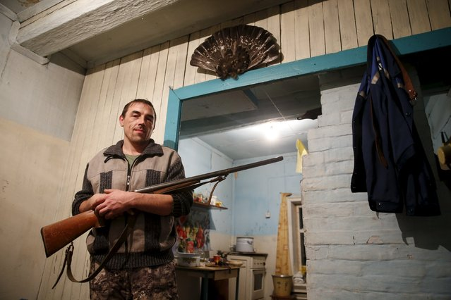 Local resident Alexander poses with a gun in his house in the village of Kalach, Sverdlovsk region, Russia October 18, 2015. (Photo by Maxim Zmeyev/Reuters)