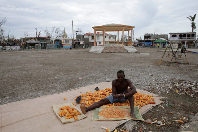 A man removes kernels from cobs of corn after Hurricane Matthew in Les Anglais, Haiti, October 14, 2016. (Photo by Andres Martinez Casares/Reuters)