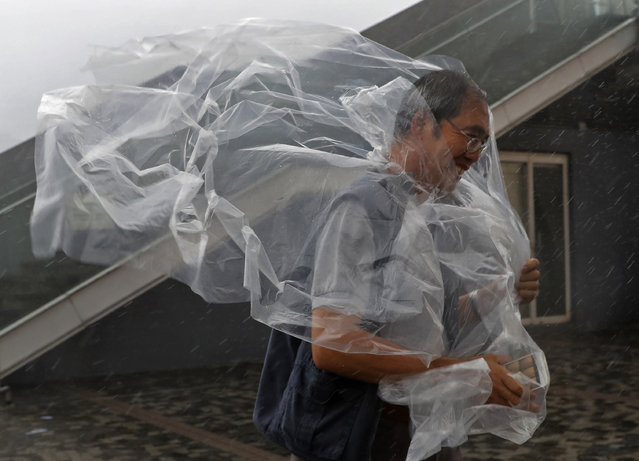 A man braves the wind on the waterfront of Victoria Habour as Typhoon Haima approaches Hong Kong, Friday, October 21, 2016. Typhoon Haima churned toward southern China on Friday after smashing into the northern Philippines with ferocious wind and rain, triggering flooding, landslides and power outages. (Photo by Vincent Yu/AP Photo)
