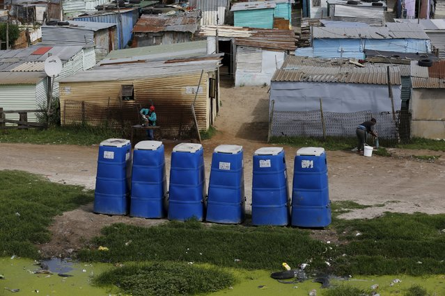 Temporary toilets stand in front of shacks in Khayelitsha township, Cape Town, South Africa, October 14, 2015. Twenty years after South Africa's first democratic elections, the slow pace of delivery of basic services remains a point of tension in some communities. (Photo by Mike Hutchings/Reuters)