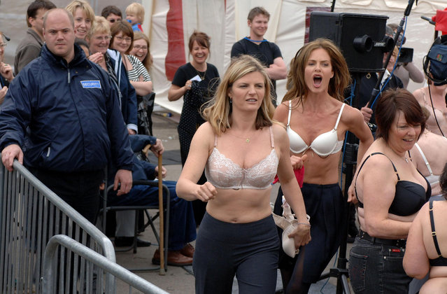 British television presenters Trinny Woodall (centre right) and Susannah Constantine (centre) lead almost 900 women in throwing their old bras into the air in Rothwell town square in Rothwell, Northamptonshire on May 7, 2007. (Photo by Clara Molden – PA Images/PA Images via Getty Images)