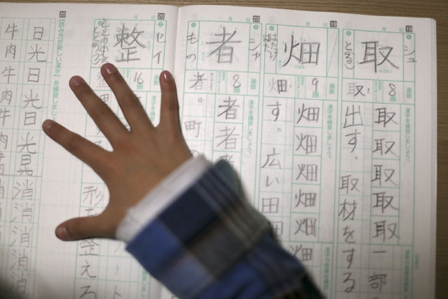 In this November 18, 2015 photo, 9-year-old Mahiro Takano, three-time Japan karate champion in her age group does her homework of Japanese letters Kanji before going to her practice of karate at home in Nagaoka, Niigata Prefecture, north of Tokyo. (Photo by Eugene Hoshiko/AP Photo)