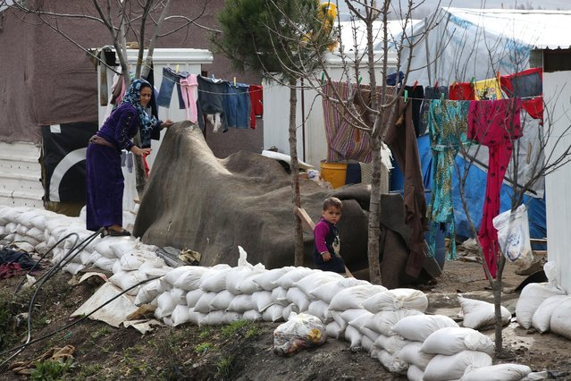 A Syrian woman, left, covers some of her belongings, as sand bags are seen set around her tent to protect it from flooding, in preparation for the possibility of a snow storm at a refugee camp in Deir Zannoun village, Bekaa valley, Lebanon, Tuesday, January 6, 2015. (Photo by Hussein Malla/AP Photo)