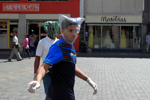 Men cover their faces with plastic bags in response to the spreading coronavirus (COVID-19) in Caracas, Venezuela on March 14, 2020. (Photo by Carlos Jasso/Reuters)