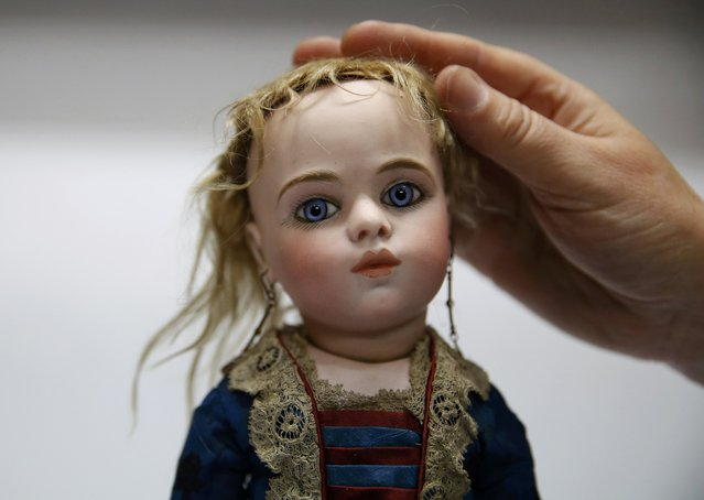 A worker adjusts the hair on a French bisque doll at the Vectis auction house in Stockton-on-Tees, Britain November 23, 2015. The doll from approximately 1880 is estimated to sell for 6000-8000 GB pounds when auctioned in a doll and teddy bear auction on Tuesday. (Photo by Phil Noble/Reuters)