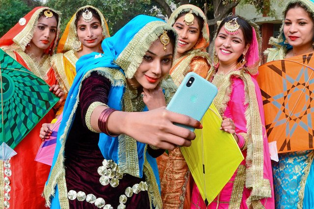 Students wearing traditional Punjabi outfits take selfies as they celebrate Lohri, the spring festival, in Amritsar on January 13, 2021. (Photo by Narinder Nanu/AFP Photo)