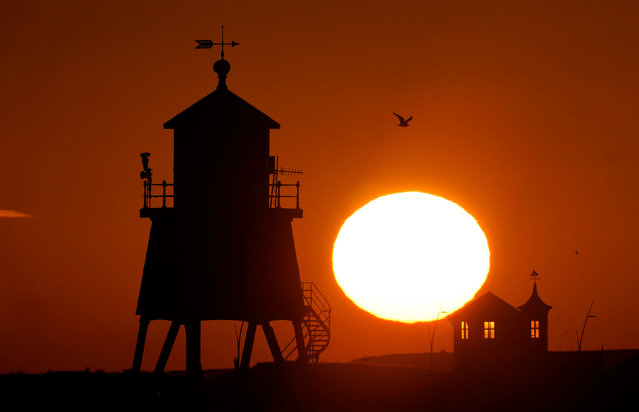 The sun rises over the Groyne in South Shields on the North East coast, United Kingdom on December 17, 2020. (Photo by Owen Humphreys/PA Images via Getty Images)