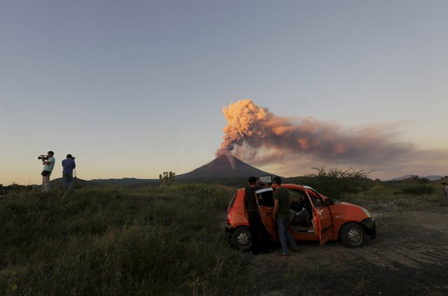 Journalists work around Momotombo volcano during an eruption as seen from Papalonal village, Nicaragua, December 2, 2015. According to the National System for Prevention, Mitigation and Attention to Disasters (SINAPRED) said that assess the situation constantly and will give their recommendations according to how the phenomenon is developed. The Momotombo volcano erupted for last time 110 years ago, local media reported. (Photo by Reuters/Stringer)