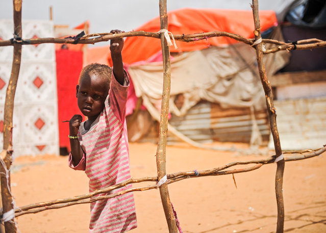 A Somali boy stands next to a structure of makeshift tent at Tawakal IDP camp in Mogadishu, Somalia, on June 19, 2018. (Photo by Mohamed Abdiwahab/AFP Photo)