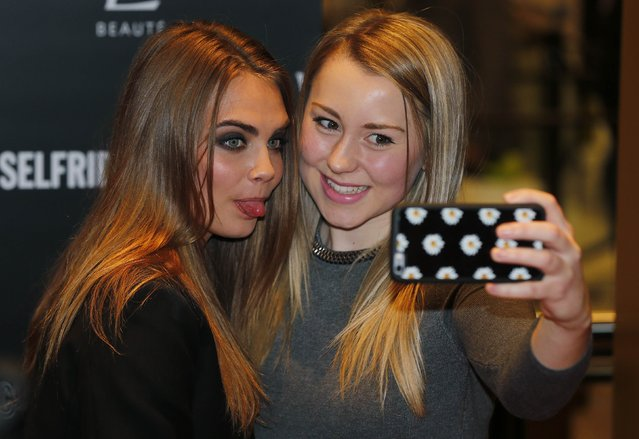 Model Cara Delevingne (L) poses for a selfie with a fan during a photo call at Selfridges department store in London January 20, 2015. (Photo by Suzanne Plunkett/Reuters)
