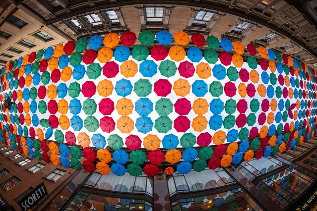 "A picture taken on October 8, 2020 shows ""The Umbrella Project"", an art installation of colourful umbrellas, over Drottninggatan shopping street in central Stockholm. The project started in 2012 during a festival in Agueda, Portugal. A group led by Portuguese artist Patricia Cunha has since then been hanging colourful umbrellas in various forms in many different places around the world. (Photo by Jonathan Nackstrand/AFP Photo)"