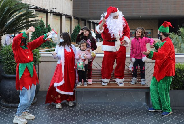A man dressed as Santa Claus, entertains children at Beirut Souks, in downtown Beirut, Lebanon on December 19, 2020. (Photo by Mohamed Azakir/Reuters)