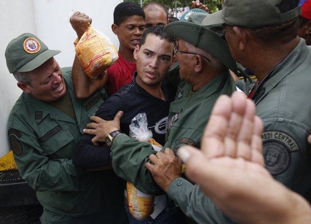 People argue with Venezuelan soldiers as they try to buy chickens at a Mega-Mercal, a subsidized state-run street market, in Caracas January 24, 2015. (Photo by Carlos Garcia Rawlins/Reuters)